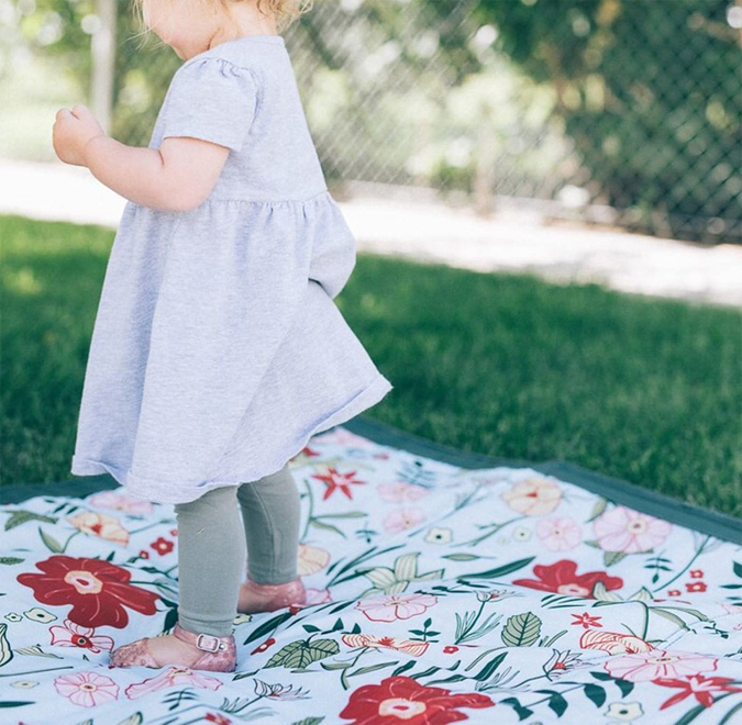 Our outdoor blankets are back!  Waterproof on one side  and soft floral nylon on the other   — they even fold up with a strap for easy transport!